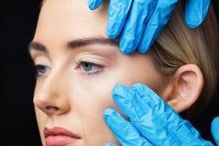 Женщина имеет рассмотрение ее кожи перед впрыской botox Стоковые Фотографии RF