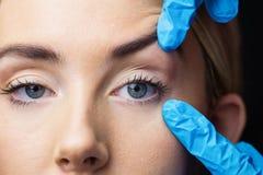 Женщина имеет рассмотрение ее кожи перед впрыской botox Стоковые Фото