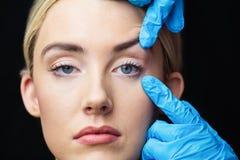 Женщина имеет рассмотрение ее кожи перед впрыской botox Стоковые Изображения