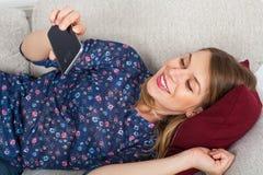 Женщина имея видео- болтовню, лежа на кресле Стоковая Фотография