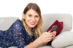 Женщина имея видео- болтовню, лежа на кресле Стоковая Фотография RF