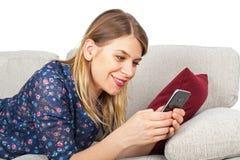 Женщина имея видео- болтовню, лежа на кресле Стоковое Фото
