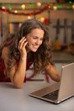 Женщина имея видео- болтовню на компьтер-книжке в кухне стоковые фото