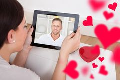 Женщина имея видео- болтовню с парнем на цифровой таблетке Стоковое фото RF