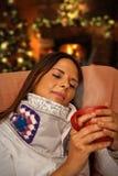 Женщина имея горячее питье усаживая около рождественской елки и камина Стоковое Изображение