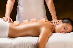 Женщина имея горячий гималайский каменный массаж в курорте стоковые фотографии rf