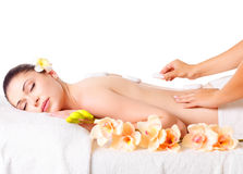 Женщина имея горячий каменный массаж в салоне спы. стоковые изображения