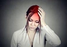 Женщина имея головную боль с ее головой в ее руке стоковые изображения