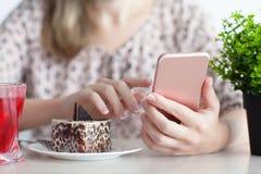 Женщина имея завтрак в кафе и держа розовый телефон стоковые изображения