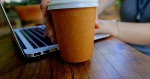 Женщина имея кофе пока использующ компьтер-книжку на внешнем кафе 4k видеоматериал