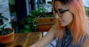 Женщина имея кофе пока использующ компьтер-книжку на внешнем кафе 4k акции видеоматериалы