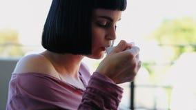Женщина имея кофе пока читающ книгу в балконе 4k акции видеоматериалы