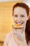Женщина имея ломтик хлеба Стоковая Фотография RF