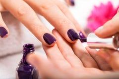 Женщина имея маникюр ногтя в салоне красоты стоковые фото