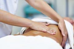 Женщина имея массаж брюшка профессиональными therapis osteopathy стоковая фотография rf