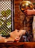 Женщина имея масло Shirodhara лить на голове в курорте Индии стоковые изображения
