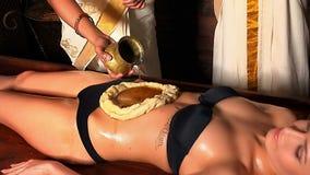 Женщина имея обработку курорта Ayurveda живота Массажируйте брюшко используя лить масло в форме теста сток-видео