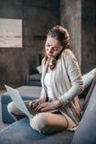 Женщина имея переговор на smartphone и печатая на компьтер-книжке дома Женщина во время офиса надомного труда стоковое фото
