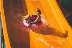 Женщина имея потеху идя вниз на водные горки Стоковые Изображения