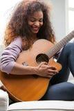Женщина имея потеху с ее гитарой стоковое изображение rf