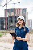 женщина инженер по строительству и монтажу Архитектор с планшетом на строительной площадке Смотреть молодой женщины, строя стоковое изображение