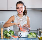 Женщина испаряясь семги и овощи Стоковое фото RF
