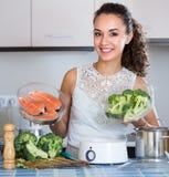 Женщина испаряясь семги и овощи Стоковые Изображения RF