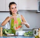 Женщина испаряясь семги и овощи Стоковое Изображение