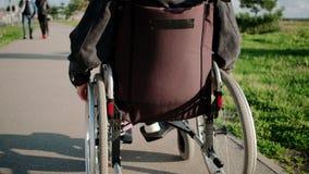 Женщина использует кресло-коляску для двигать outdoors в солнечном дне, заднем взгляде сток-видео