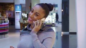 Женщина использует мобильный телефон на покупках стоковая фотография rf