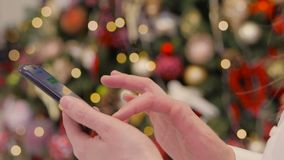 Женщина использует портативное устройство для просмотра социальных сетей пока держащ смартфон в ее руках против ярких светов видеоматериал