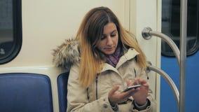 Женщина использует Apps или пишет сообщения к Smartphone в поезде метро подземном акции видеоматериалы