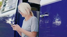 Женщина использует smartphone Сидит на шаге фиолетового ретро фургона видеоматериал