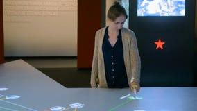 Женщина используя взаимодействующий дисплей сенсорного экрана стоковое фото