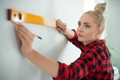 Женщина используя выравнивающ инструмент дома стоковое изображение rf