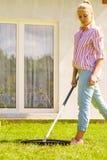 Женщина используя грабл для того чтобы очистить вверх сад Стоковая Фотография RF
