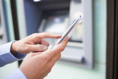Женщина используя ее мобильный телефон перед банкоматом стоковая фотография