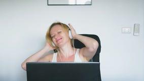 Женщина используя ее ноутбук сидит на таблице, смеяться и говорить взволнованности людские нарисованная наркоманией белизна векто видеоматериал