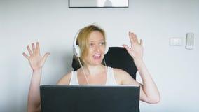 Женщина используя ее ноутбук сидит на таблице, смеяться и говорить взволнованности людские нарисованная наркоманией белизна векто сток-видео