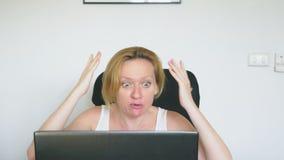 Женщина используя ее ноутбук, сидя на таблице, сердитый и раздражанный, клянется взволнованности людские Концепция наркомании инт акции видеоматериалы