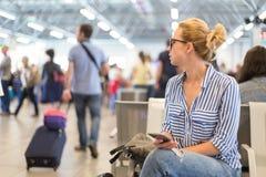 Женщина используя ее сотовый телефон пока ждущ для восхождения на борт самолета на стробах отклонения на международном аэропорте Стоковое Фото