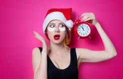 Женщина используя заплату глаза для ее глаза в шляпе Санта Клауса с сигналом тревоги Стоковое Фото
