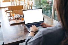 Женщина используя и печатающ на ноутбуке с экраном пробела белым настольным на деревянном столе стоковая фотография