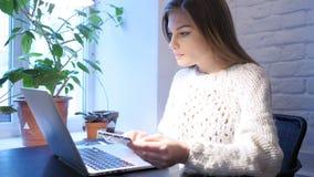 Женщина используя карточку банка для онлайн оплаты в офисе акции видеоматериалы