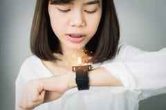 Женщина используя команды голосом в цифровых часах в выдвижениях дисплея и технологии в сообщение стоковая фотография