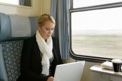 Женщина используя компьтер-книжку перемещая регулярным пассажиром пригородных поездов поезда стоковое фото rf