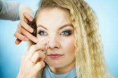 Женщина используя масло закрывая ткани на модели Стоковое фото RF