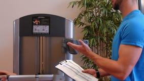 Женщина используя машину весов в спортзале с тренером видеоматериал