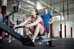 Женщина используя машину rowing пока инструктор готовя Стоковые Фотографии RF