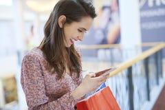 Женщина используя мобильный телефон во время покупок в городе стоковая фотография rf